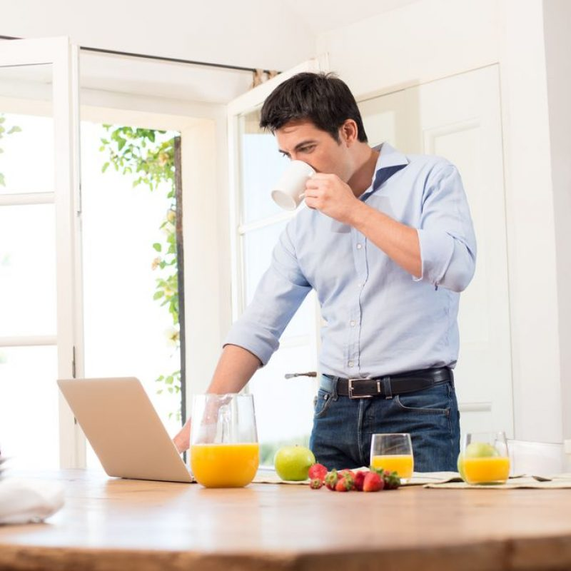 20837534 - portrait of young man using laptop while having breakfast